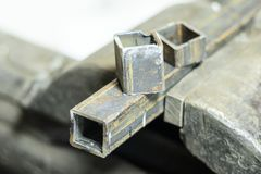 металл схватывает в их зажал квадратную трубку все еще часть на верхней части Малая глубина отрезка стоковые фото