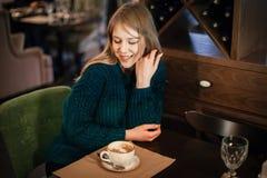 Мечты и улыбки девушки в кафе на таблице с чашкой кофе стоковая фотография
