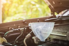Механик автомобиля заменяя свежее масло в двигатель на станции ремонтных услуг обслуживания Селективный фокус стоковые изображения