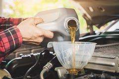Механик обслуживать обслуживания автомобиля лить новую смазку масла в двигатель автомобиля Селективный фокус стоковое фото