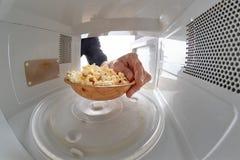 Микроволна и шар заполненные с попкорном Прибор для нагревать блюда с пользой myocual волн стоковые фотографии rf