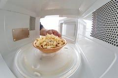 Микроволна и шар заполненные с попкорном Прибор для нагревать блюда с пользой myocual волн стоковые фото