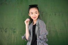 Милая выведенная из азиатская девушка думая и усмехаясь около зеленой стены смотря к стороне стоковое фото rf