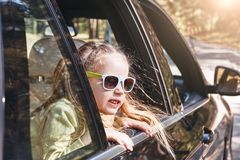 Милая жизнерадостная маленькая кавказская девушка сидя внутри автомобиля, смотрящ вне окно и усмехаться Поездка семьи стоковая фотография