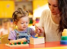 Милая игра младенца с человеком осуществляющим уход внутри помещения стоковое изображение