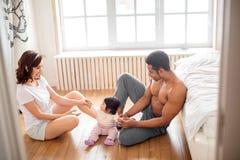 Милая маленькая девочка сидя между ее родителями играет с ними стоковые фотографии rf