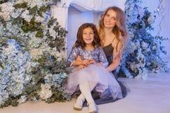Милая маленькая девочка с мамой внутри помещения стоковое изображение