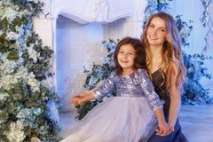 Милая маленькая девочка с мамой внутри помещения стоковые фото