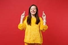 Милая молодая женщина в ожидании свитера меха на особенный момент, держа пальцы пересекла, глаза закрыла, делающ желание изолиров стоковые фотографии rf