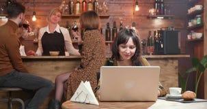 Милая молодая женщина печатая сообщение на ее ноутбуке и усмехаться сток-видео