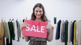 Милая молодая женщина представляет с сумкой продажи в комнате одежды сток-видео