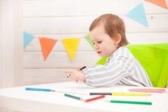 Милая притяжка ребенка с красочными карандашами на таблице стоковые фото