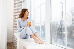 Милая девушка брюнета в свет-голубой пижаме сидит на windowsill и держит стекло свежего сока в ее руках стоковое изображение
