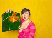Милая девушка в розовом striped свитере с большим зеленым подарком со смычком на желтой предпосылке студии стоковое изображение