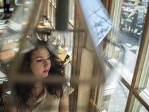 Милая девушка с вьющиеся волосы сидит на таблице в кафе и смотрит вне окно стоковое изображение