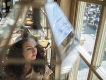 Милая девушка с вьющиеся волосы сидит на таблице в кафе и смотрит вне окно стоковая фотография rf