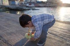 Милые 2 лет старого малыша играя с небольшими игрушкой и корзиной цыпленка с 2 пасхальными яйцами на море doc стоковые фото