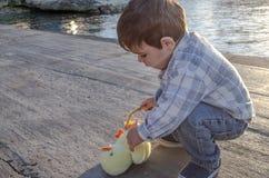 Милые 2 лет старого малыша играя с небольшими игрушкой и корзиной цыпленка с 2 пасхальными яйцами на море doc стоковое изображение