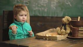 Милый маленький кавказский мальчик есть пиццу Мальчик есть пиццу на деревянной предпосылке Принципиальная схема питания пицца вку видеоматериал