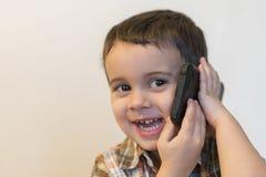 Милый мальчик говоря мобильным телефоном на светлой предпосылке Счастливое положение мальчика и говорить на смартфоне дома стоковое изображение