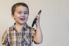 Милый мальчик говоря мобильным телефоном на светлой предпосылке Счастливое положение мальчика и говорить на смартфоне дома стоковое изображение rf