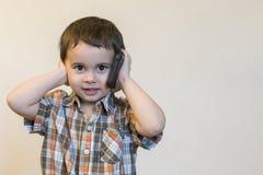 Милый мальчик говоря мобильным телефоном на светлой предпосылке Счастливое положение мальчика и говорить на смартфоне дома стоковая фотография