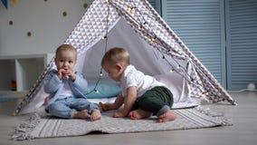 2 милых младенца поставили остановку около шатра детей и едят печенья сток-видео