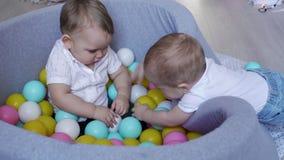 Младенец комплектует вверх пластиковый шарик от другого мальчика который сидит в бассейне шариков сток-видео