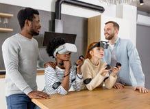Многокультурная группа в составе друзья играя игры используя стекла виртуальной реальности стоковое изображение