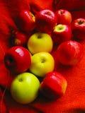 Много красивых желтых и красных яблок на апельсине стоковое изображение