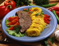 Meat steak from beef with noodles. And vegetables on a blue plate royalty free stock images