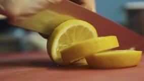 Мужская рука отрезая лимон с большим концом ножа шеф-повара вверх Здоровое приготовление пищи в современных ресторане или кафе видеоматериал