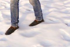 Мужские ноги в коричневых ботинках и голубых джинсах идут на снег скопируйте космос Шаг Wirst после катастрофы снега стоковые фото