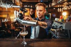 Мужской бармен лить напиток от шейкера стоковые изображения
