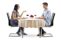 Мужчина и женские подростки сидя на таблице и говорить ресторана стоковое фото