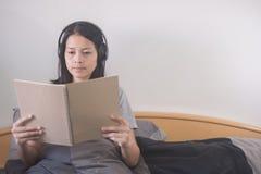 Музыка красивой азиатской женщины слушая с наушниками и книгой чтения ослабляя на кровати стоковое фото rf