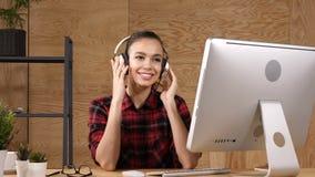 Музыка расслабленной коммерсантки слушая в наушниках на перерыве работы Посмотрите в камеру акции видеоматериалы