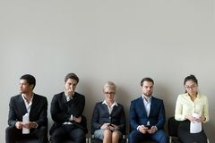 Мульти-этнические кандидаты сидя в линии очереди строки подготавливая для интервью стоковые изображения rf