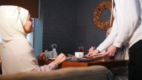 2 мусульманских женщины сидя в ресторане Официант приносит заказ сток-видео