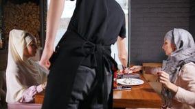 2 мусульманских женщины сидя в ресторане Официант в черной форме приносит заказ видеоматериал
