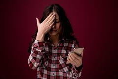 Мобильный телефон удерживания девушки или молодой женщины как жертва преследовать интернетом злоупотребленная в cyberbullying или стоковые фотографии rf