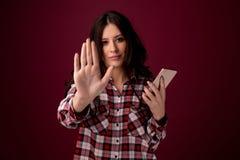 Мобильный телефон удерживания девушки или молодой женщины как жертва преследовать интернетом злоупотребленная в cyberbullying или стоковое фото
