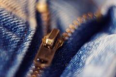 Молния сделанная латуни на грубых голубых джинсах прикрепила стоковые изображения