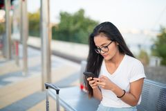 Молодая азиатская туристская женщина сидя и используя телефон пока ждущ поезд стоковые изображения