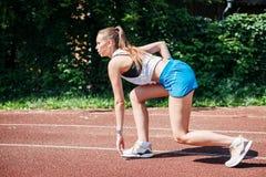 Молодая атлетическая женщина подготавливая побежать на стадионе, outdoors Взгляд от стороны concept healthy lifestyle стоковая фотография
