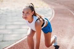 Молодая атлетическая женщина подготавливая побежать на стадионе, outdoors Концепция здорового образа жизни стоковое фото