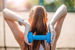 Молодая атлетическая девушка делая тренировки с гантелями Представлять на спортивной площадке женщина гонки смешанной модели прел стоковая фотография