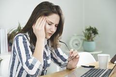 Молодая бизнес-леди имеет головную боль в офисе стоковое фото