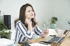 Молодая бизнес-леди имея боль шеи стоковое изображение