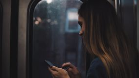 Молодая женщина брюнета идя где-то в двигая метро Девушка используя смартфон стоя около окна на заходе солнца акции видеоматериалы